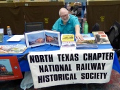Claude Doane puts out another stack of BNSF calendars. BNSF donated all the calendars for the club to give away.
